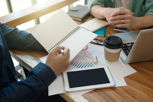 ホームオフィスでメモ帳でビジネスチームブリーフィングマーケティング戦略 Premium写真