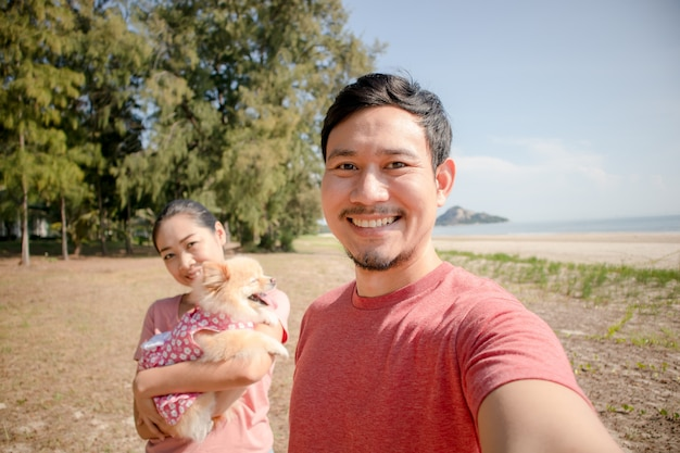 幸せなアジアカップルとビーチで子犬。 Premium写真