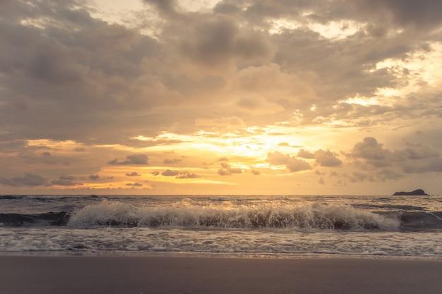 黄金の夕焼け穏やかな空ときれいなビーチ。 Premium写真