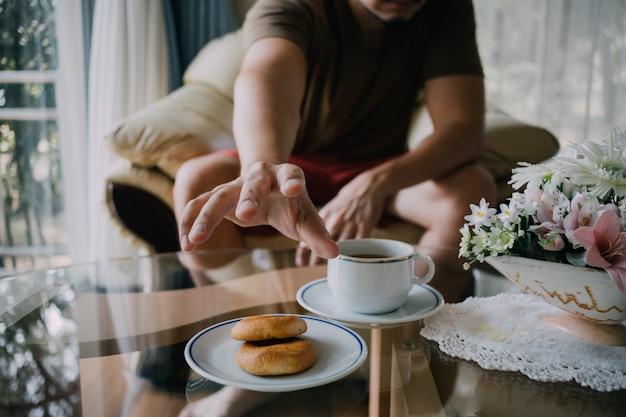 クッキーとコーヒーをつかむために達する男。 Premium写真