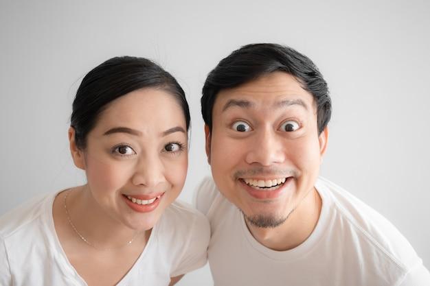 Удивлен над парой смешное лицо в белой футболке и белом фоне. Premium Фотографии