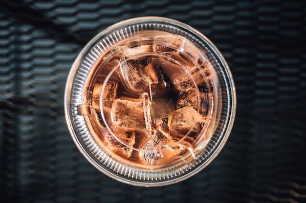 黒いテーブルの上のプラスチック製のガラスのアイスチョコレート。 Premium写真