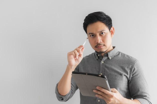 深刻な思考起業家実業家は、灰色の背景を持つ彼のタブレットに取り組んでいます。 Premium写真