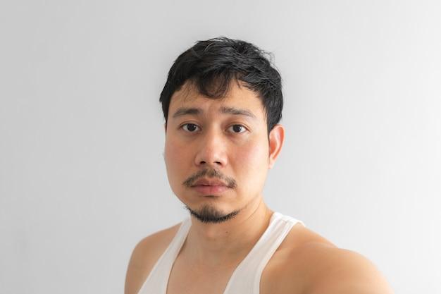 灰色の背景上の男のかわいそうな顔。絶望的な生活のコンセプトです。 Premium写真