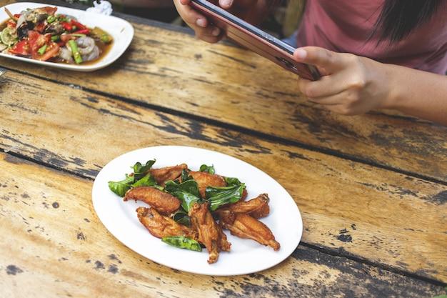 女性の手がスマートフォンでテーブルの上の地元のタイ料理の写真を撮る Premium写真