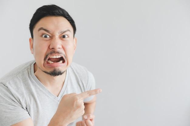 Сердитое лицо человека в серой футболке с рукой указывают на пустое пространство. Premium Фотографии