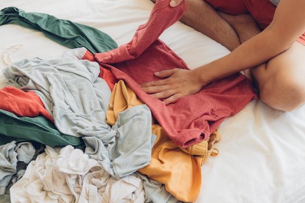 男はベッドの上で服を折って整理しています。 Premium写真