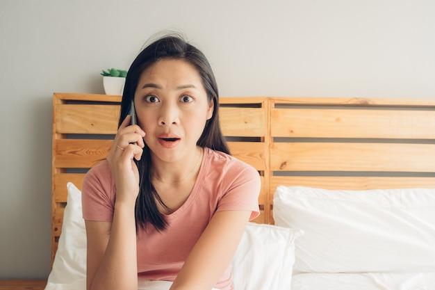 ショックを受けたと驚いた女性は彼女のベッドで電話での会話をしています。 Premium写真