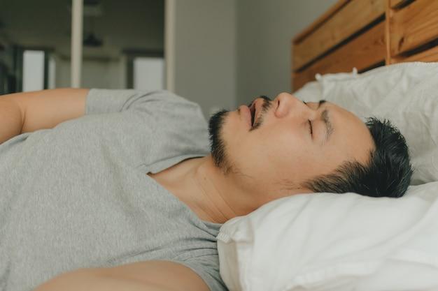 Крупным планом человек спит на кровати с храпом Premium Фотографии
