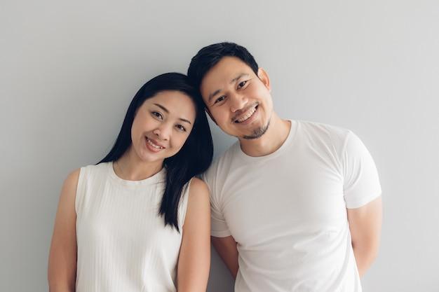 Счастливый любовник пар в белой футболке и серой предпосылке. Premium Фотографии