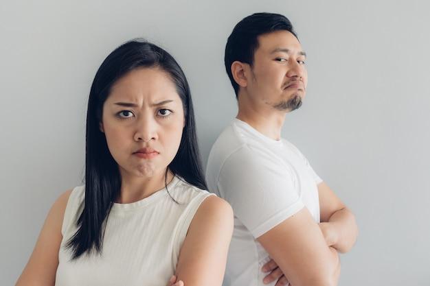 Сердитый любовник пар в белой футболке и серой предпосылке. Premium Фотографии