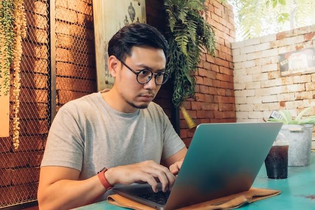 Человек работает на своем ноутбуке в кафе. Premium Фотографии