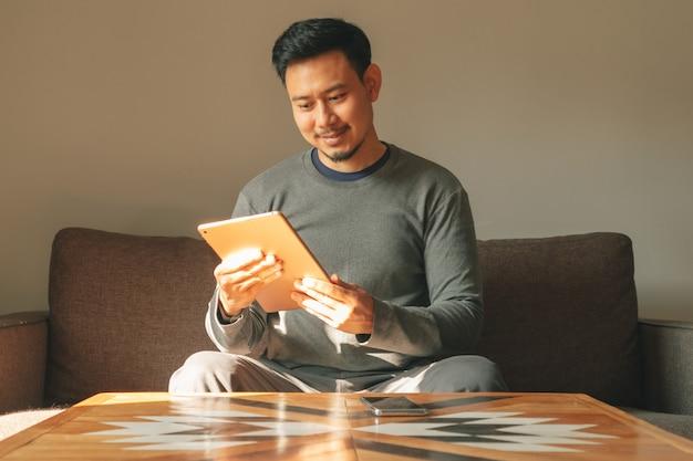 男は彼のリビングルームのアパートで彼のスマートタブレットデバイスを使用しています。 Premium写真