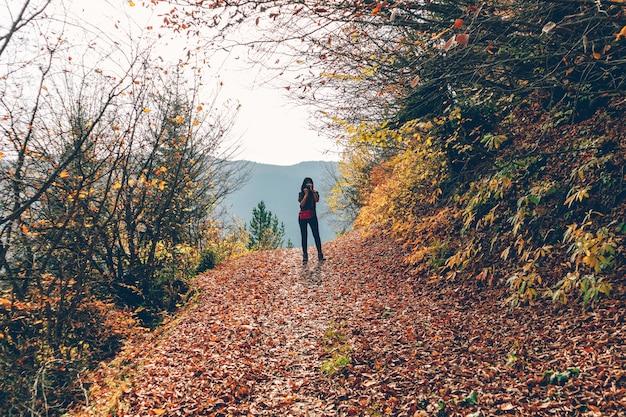 女性は、秋に丘でハイキングしながら自然の風景写真を撮っています。 Premium写真
