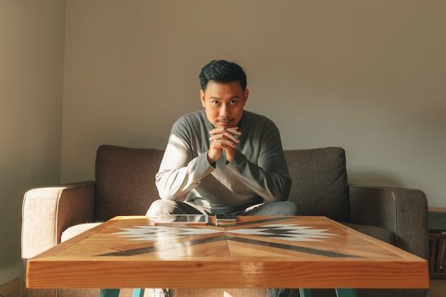 男は彼のリビングルームのソファに座って、朝はリラックスした感じ。 Premium写真