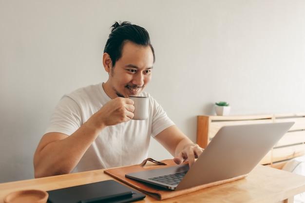 Счастливый человек работает в своей квартире Premium Фотографии