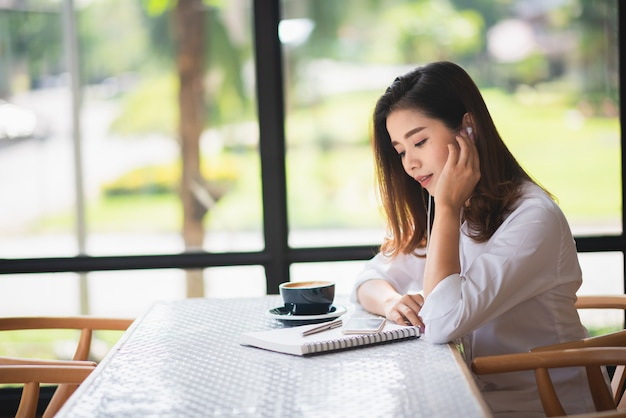 美しい少女はカフェで音楽を聴くといくつかのコーヒーを飲む Premium写真