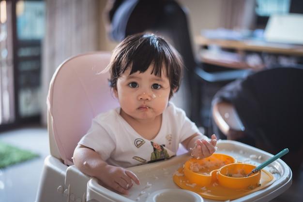 テーブルで汚れて食べるかわいい赤ちゃんの肖像画 Premium写真