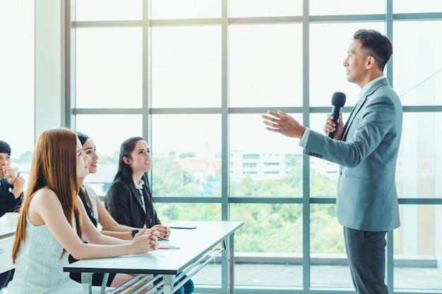 Тренер азиатских деловых людей дает представление Premium Фотографии