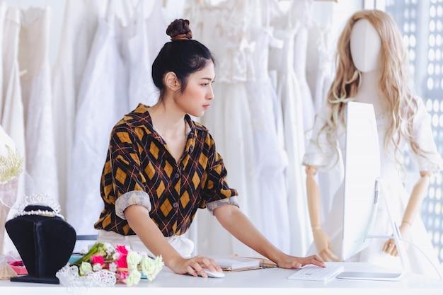アジアのデザイナーの結婚式のファッション店で働いて Premium写真