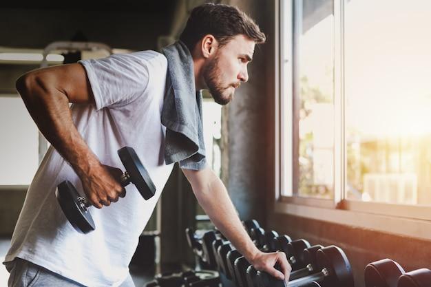 クローズアップ男性健康的なダンベルトレーニングを保持しているとジムフィットネスで体を構築 Premium写真