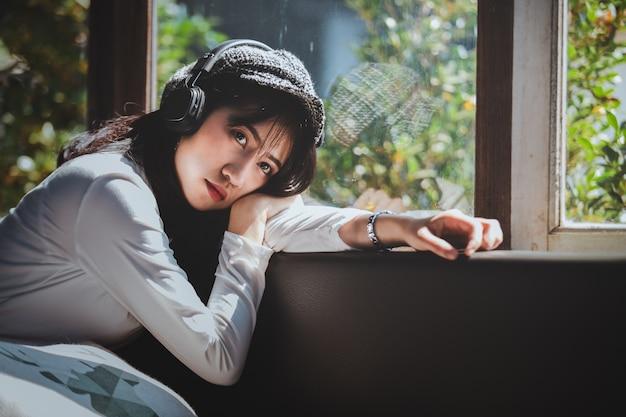 Эмоции чувствуя молодая девушка грустно слушать музыку, глядя в окно Premium Фотографии