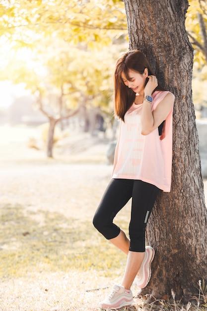 アジアの美しい若い女性の公園でリラックスした運動 Premium写真