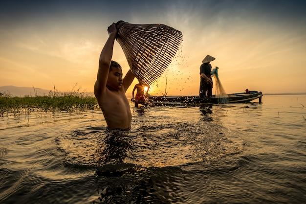 魚トラップを使って古代の魚を見つける方法と人々は幸せに生きる。 Premium写真