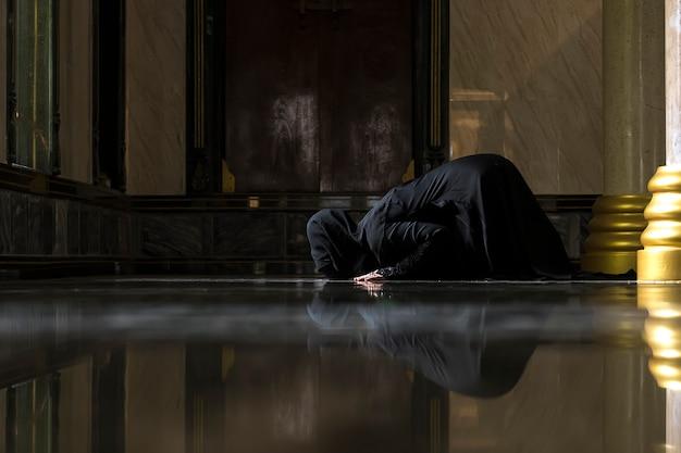 黒いシャツを着ているイスラム教徒の女性イスラム教の原則に従って祈りをしています。 Premium写真