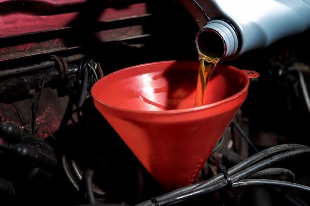給油と注油エンジン、メンテナンス、および性能にオイルを補給します。 Premium写真