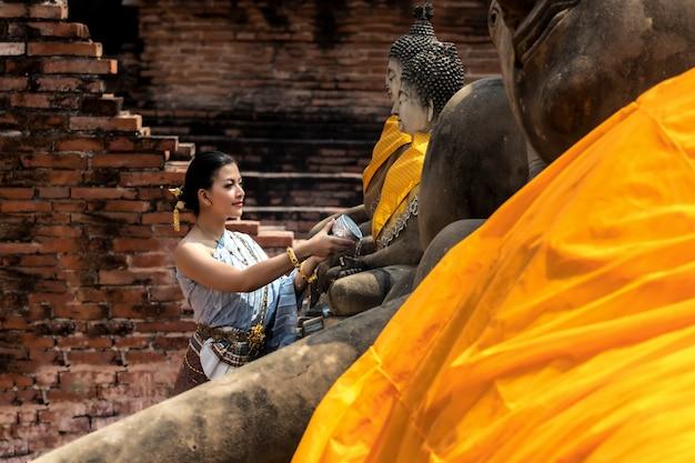 タランドフェスティバルアジアの女性がタイでソンクラーン日水祭りで仏水浴びをするタイの伝統衣装を着ています。 Premium写真