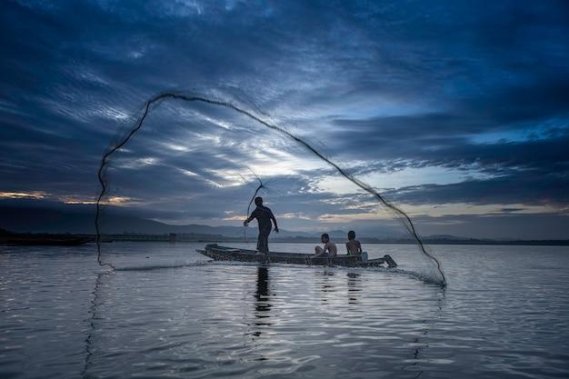 漁師のキャスティングは、早朝から木製のボート、古い提灯、網で釣りに出かけています。コンセプト漁師のライフスタイル。 Premium写真