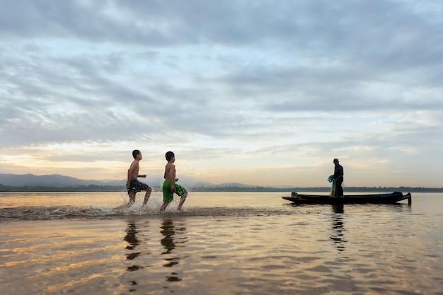 子供の漁師はまだ漁村を投げかけています。子供たちの笑顔を幸せにします。漁師は古い木造りのボートに乗るでしょう。 Premium写真