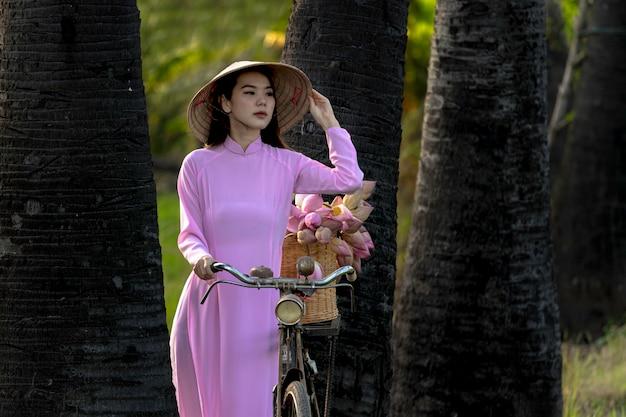 アジアのかわいい女の子ベトナムアオザイの伝統的な衣装を着てベトナムのピンクのドレス。アジアの女性ベトナムは蓮の花のバスケットの後に店に女の子のトロリーバイクです Premium写真