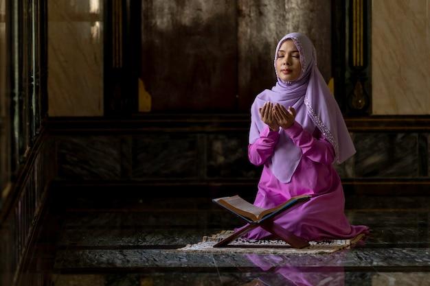 イスラムの祈りをしている紫色のシャツを着ているイスラム教徒の女性。 Premium写真