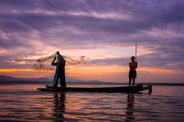 漁師キャスティングは、早朝に木製のボート、古いランタン、ネットで釣りに出かけます。コンセプトフィッシャーマンズライフスタイル Premium写真