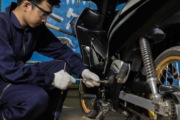 人々はオートバイを修理していますレンチとドライバーを使用して作業します。 Premium写真