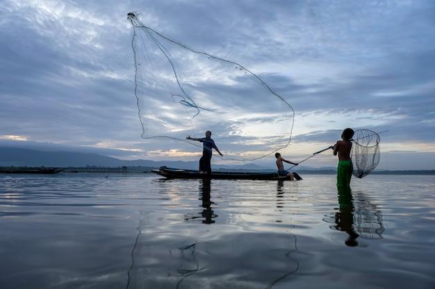 画像はシルエットです。漁師キャスティングは、木製ボート、古いランタン、ネットで早朝に釣りに出かけます。コンセプトフィッシャーマンズライフスタイル Premium写真