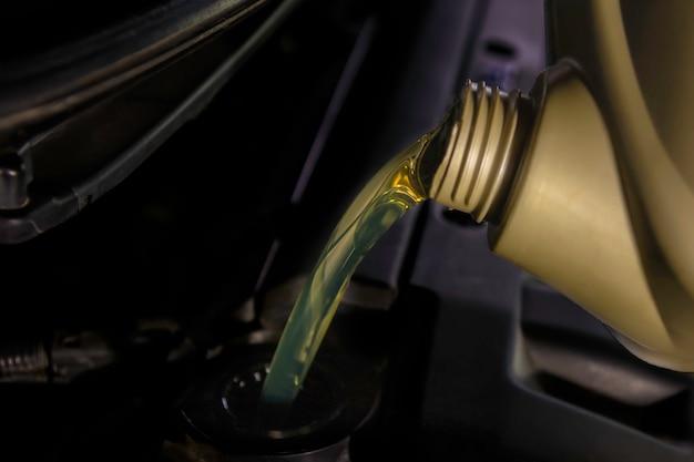 オイルの補給と注油エンジン、メンテナンス、およびパフォーマンスにオイルを充填します。 Premium写真