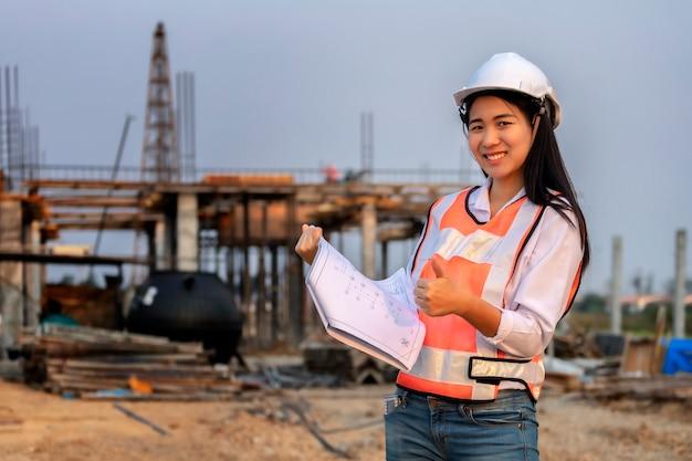 Архитектор здания плана бумаги инженера-строителя азиатской женщины нося белый шлем безопасности Premium Фотографии