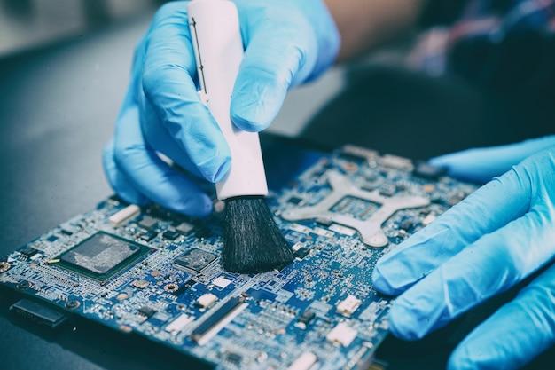 アジアの技術者が汚れやほこりのマイクロ回路のメインボードコンピューティングを修理およびクリーニングします。 Premium写真