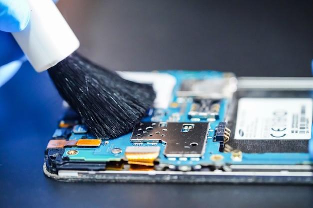 アジアの技術者の修理とブラシでスマートフォンの汚れたマイクロ回路メインボードのクリーニング。 Premium写真