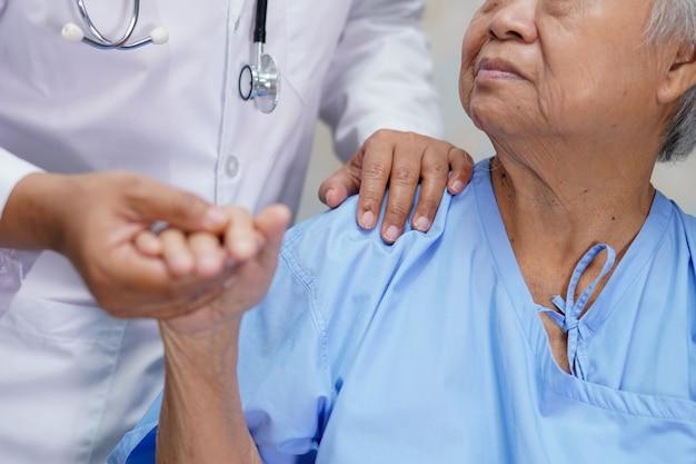 アジアの年配の女性患者に触れるアジアの看護師理学療法士医師 Premium写真