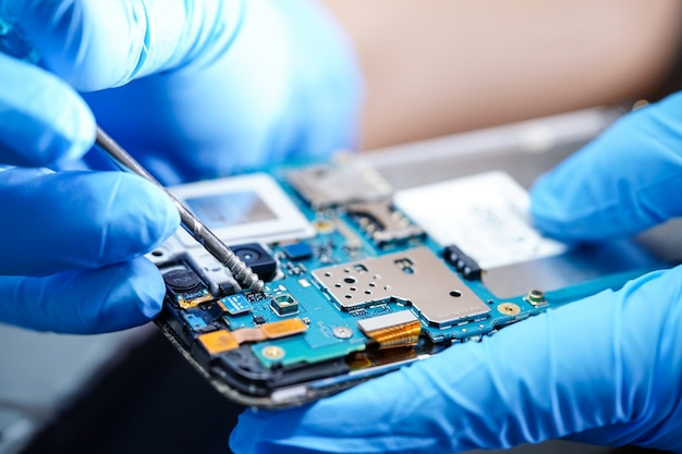 アジアの技術者がスマートフォンのマイクロ回路メインボードを修復します。 Premium写真