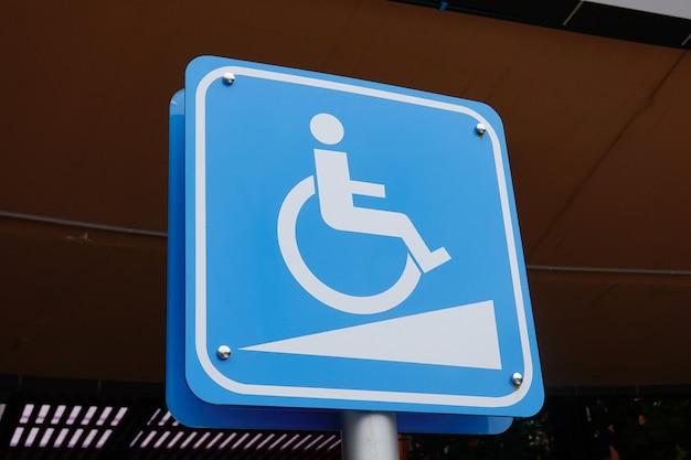 Голубой гандикап на стоянке автомобиля знак на открытом воздухе для инвалидов и инвалидной коляски. Premium Фотографии
