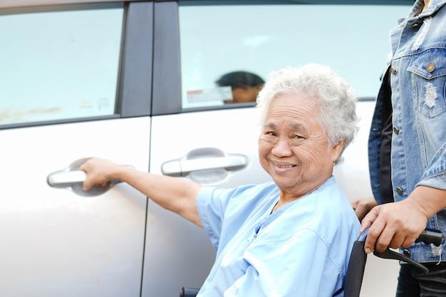 Азиатский старший пациент женщины сидя на кресло-коляске подготавливает получить к ее автомобилю. Premium Фотографии