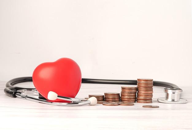 赤いハートとコインと聴診器。 Premium写真