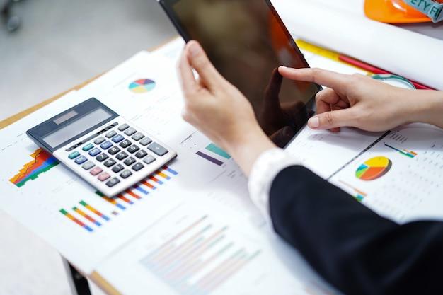 Таблетка прессы бухгалтерии с калькулятором и диаграмма для работы в офисе. Premium Фотографии