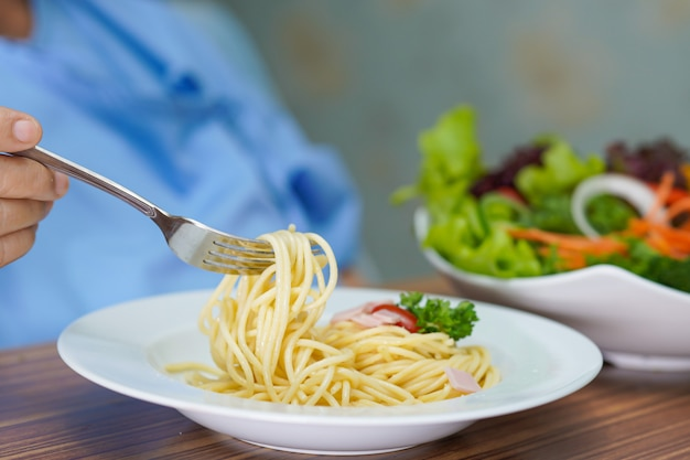 カルボナーラスパゲッティとサラダを食べるアジアの年配の女性患者。 Premium写真
