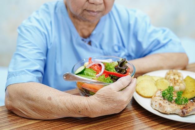 アジアの年配の女性患者が病院で朝食を食べる。 Premium写真
